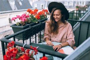 Femme sur un balcon fleuri en train d'écrire un texte avec ponctuation