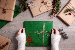 Mains de femme qui dépose un cadeau pour entrepreneur écoresponsable